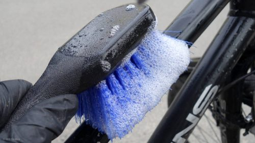The bicycle is washed off with a brush and warm water with dishwashing detergent