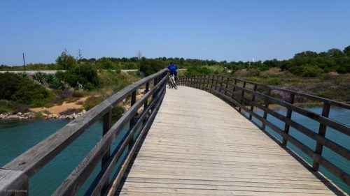 The bike path Ecovia do Litoral leads over a crooked bridge at Tavira